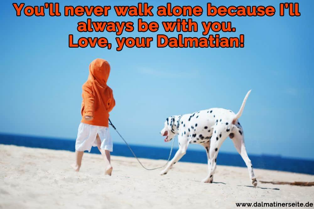 Ein Junge schlendert am Strand mit seinem Dalmatiner