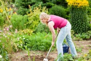 Frau beim Hund begraben im Garten