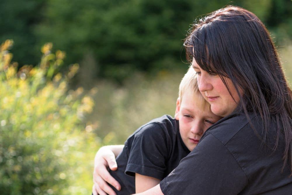 Mama tröstet ein Kind nachdem der Dalmatiner eingeschläfert wurde.