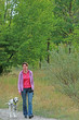 Mature woman is walking a dalmatian dog in nature environment